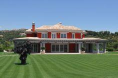 Vista del jardín trasero de esta villa de lujo con decoración de piedra artificial de color gris.