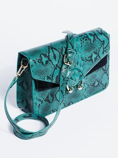 Around Town Crossbody | Faux leather crossbody featuring a removable and adjustable long strap for a carry-as-a-clutch option.    * Snap button closure   * Front metal ring accent   * Lined inner with small compartment for simple storing