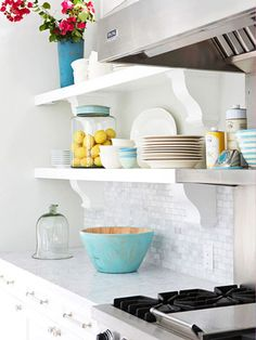 I love the open white shelving on the backsplash with the beautiful blue accents