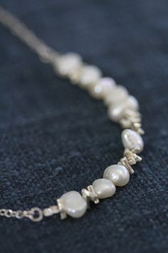 """This necklace is made of 9 irregular pearl beads, alternated with handmade silver sprinkle-shape beads and silver chain. It closes with a simple silver hook. It is very delicate and lightweight, pearls make it suitable for weddings, especially for bridesmaids jewelry.  The necklace can be matched to a similar bracelet and earrings, making it thus a beautiful jewelry set."