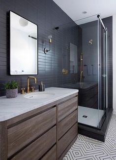 Beautiful modern bathroom boasts an oak dresser-like washstand topped with a carrera marble countertop fitted with an oval sink fixed under a gold faucet positioned beneath a curved aged steel mirror mounted on matte black grid wall tiles next to a black and gold wall sconce.