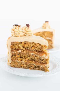 Slice of carrot cake with caramel buttercream on a white dessert plate showing the buttercream and caramel layers.
