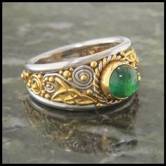 Custom 14K White and 18K Yellow Gold Celticring. This ring is filled with spirals and knotwork, and an elegant twist around the center set Emerald cabochon. This ring is currently available for sale i