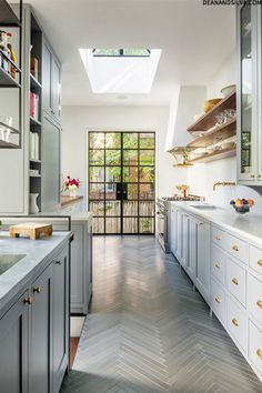 Herringbone floor, Crittal doors, and open shelving for maximum style in this narrow kitchen