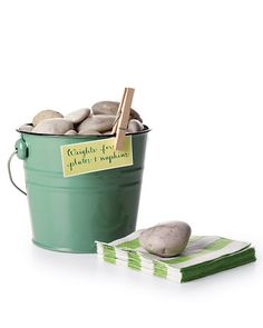 River Rock Paperweights - Pretty paper goods are no match for an unruly summer breeze at an outdoor party. River rocks (available by the bag at garden centers) help keep plates and napkins where they belong, even after they've left the serving table. Rinse them off, then pile them in a bucket on the buffet table for guests to grab along with their utensils; you'll avoid having to chase fly-a-ways.