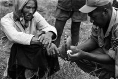 Um médico atende um cívil vietnamita ferido. Nomes, data e local desconhecido