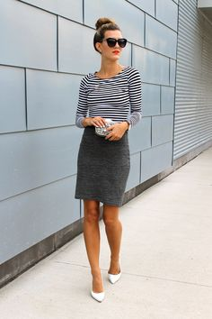 Chica usando una falda de lapiz color gris y una blusa negra con rayas