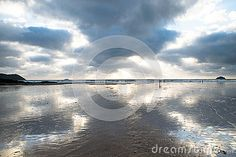 Sunset over Polzeath beach North Cornwall showing reflections of the clouds in…