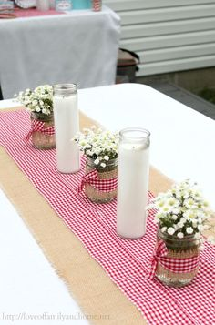 Inexpensive jar candles from the dollar tree and mason jars wrapped in burlap with red gingham bow. Simple, easy table decor for western/cowboy themed party.: