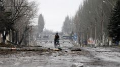 civilian bike usage in Ukraine: A resident rides his bicycle through a destroyed street in the town of Vuhlehirsk, Ukraine, Friday, Feb. 6, 2015