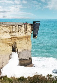 """Giving new meaning to the term """"cliffhanger,"""" Australia's Modscape has presented a thrilling conceptual design entitled """"Cliff House""""—a five-story home inspired by the shape of barnacles clinging to a ship. The three-bedroom, two-bath interior is minimally furnished, emphasizing the home's intrinsic connection to the ocean and the horizon. Adding to the sensation of hovering above the ocean, the ground floor features an outdoor patio space with an outdoor kitchen and a jacuzzi."""