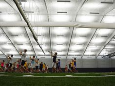 The Hawkeye Marching Band rehearses Wednesday at its new indoor practice facility in Iowa City featuring prescription athletic turf with yard markers, and acoustic panels line the ceiling to enhance sound for the band.