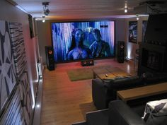 "The term ""home theater"" is commonly thrown around to describe almost any living room HDTV+speaker combination, but true movie theater performance and comfort at home is difficult and pricey to recreate. But this DIY home theater project does successfully bridge the realm of a real world space with loftier planning, resulting in an immersive and comfortable big screen experience on two levels..."