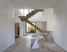 minimalistic staircase calls for sleek ...smooth ..chic...sculptural table...perfection...