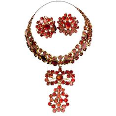 """'Queen Anne' Choker and Earrings, England, c 1740. Almandine garnets set in gilt metal are fashioned into a striking pair of earrings and choker with drop, which can be removed. The choker is tied on with a ribbon. Much of the jewelry of this period was set with pastes. These pieces are unusual in that gemstones were used. Though called """"Queen Anne"""", jewelry of this type was actually made some 30 odd years after her reign."""