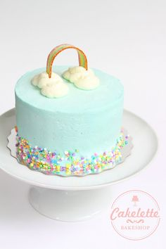 A simple birthday cake with sky blue buttercream, a candy stripe rainbow, whipped cream clouds and rainbow confetti!