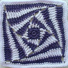 crochet square in blues - this mathematical pattern is called the 'Curve of Pursuit'