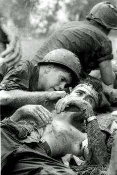 With sniper fire still passing overhead, medic James E. Callahan of Pittsfield, Mass., treats a U.S. infantryman who suffered a head wound when a Viet Cong bullet pierced his helmet during a three-hour battle in war zone D, about 50 miles northeast of Saigon, June 17, 1967. Thirty-one men of the 1st Infantry Division were reported killed in the guerrilla ambush, with more than 100 wounded. (AP Photo/Henri Huet)
