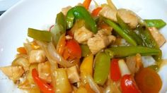 Carrots and red and green bell peppers add lots of color to this classic sweet pineapple and sour soy-vinegar chicken stir fry with just a whiff of ginger.