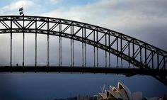 An Australian national flag and a New South Wales state flag fly at half-mast atop the Sydney Harbour Bridge.