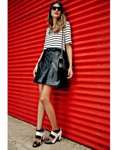 Mariana Cassou, co-founder e buyer do Gallerist, veste look preto e branco em mix de top listrado, minissaia de couro e sapatos P&B.