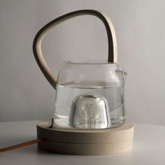 This kettle by Ecole Nationale supérieure d'Art et de Design de Saint-Etienne graduate Estelle Sauvage uses a light bulb to heat water for a cup of tea. The incandescent bulb is mounted on a wooden base, while the glass jug has a recess to house the bulb close to but separate from the water. It