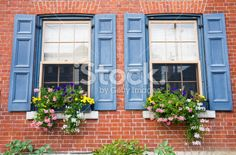 A red brick home with blue shutters around the windows and with. Shutters Brick House, Outdoor Window Shutters, Blue Shutters, Exterior Paint Schemes, Exterior House Colors, Orange Brick Houses, Red Brick Exteriors, Shutter Colors, Front Door Paint Colors