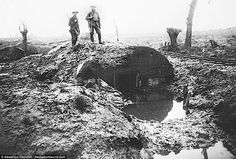 Two men are seen standing on top of a dugout in Flanders which has been flooded. British g...