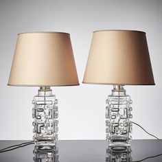 Swedish Modernist Ice Glass Table Lamps by Pukeberg Glass Company. Pair of Mid-century Modern clear, textured, glass lamps with an abstract pattern.