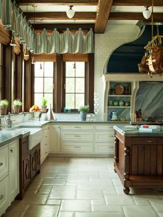 Kitchen with a chateau patterned limestone floor and blue veined quartzite backsplash. Interiors by Florida design firm Taylor & Taylor. See the whole home: http://www.deringhall.com/daily-features/contributors/dering-hall/tour-a-french-country-lakeside-estate-in-florida-with-interiors-by-taylor-and-taylor