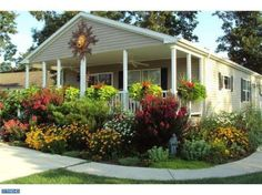 Manufactured home porch idea with gorgeous porch landscaping. Truly beautiful! Found on MobileHomeLiving.org