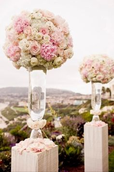 Pretty arrangements for pedestals. Personally, I'd add a drop of red food coloring to the water to make it pink.