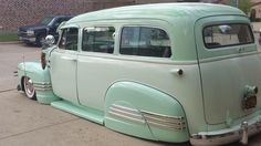 Slammed vintage Advanced Design Chevy Suburban in sea foam green and a green tinted white and rocking the deluxe trim and rear fender skirts.