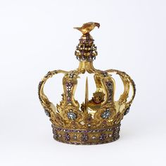 Crown  Place of origin: Portugal (made)  Date: ca.1750 (made)  Materials and Techniques: [case] Diamonds, emeralds and rubies set into a gold crown with chased rococo scrolls  Credit Line: The Rosalinde and Arthur Gilbert Collection on loan to the Victoria and Albert Museum, London  Museum number: LOAN:GILBERT.69:3-2008  Gallery location: Silver, room 89, case 2, shelf 1
