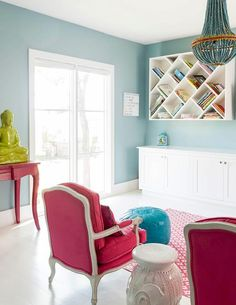 Red and turquoise blue playroom features walls painted blue lined with a wall-mount cross cut bookcase over a wall of toy cabinets.