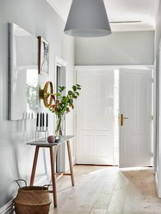 The norsuHOME - Hallway Photographer: Lisa Cohen Stylist: Beck Simon  Paint: Dulux Tranquil Retreat Flooring: Godfrey Hirst  Doors: Corinthian Doors  Products: Louis Poulson Above Pendant Cote Salt Print GlobeWest Console, By Lassen Candle Holder, Menu Mirror, Love Warriors Withering print, Olli Ella Belly Basket (all available at www.norsu.com.au)