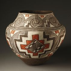A LAGUNA POLYCHROME JAR with a concave base, high shoulder and tapering neck, painted in orange and dark brown against a chalky white slip, with an encircling frieze enclosing concentric stepped devices, the neck with a series of finely striped scrolls.   height 12 1/2 in.
