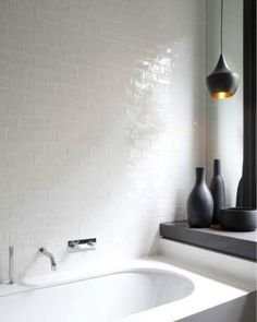 tumbled white tile, dark Tom Dixon pendant light, white bathtub