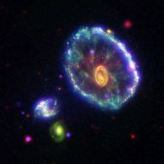 With colors reminiscent of Faberge, the Cartwheel galaxy stands out against a backdrop of other brightly-colored galactic bodies. This galaxy's Easter egg appearance's due to false colors representing various wavelengths of light — ultraviolet(blue), B-band visible light(green), infrared(red), and x-ray(purple).  This galaxy's 'rings' are aftermath of the Cartwheel's collision w/ another galaxy 100 million years ago. The neon blob & green spiral (background) are two other galaxies.
