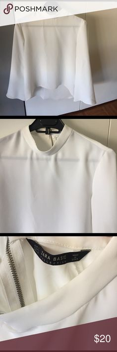 Zara blouse Never worn with tags. White asymmetrical blouse with silver zip closure on the back. There is one small mark on the back near the top. Sleeves are slightly flared and 3/4 length. Zara Tops Blouses