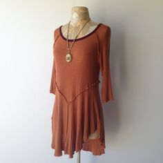 Free people golden orange layering top Gorgeous orange/brown Intimately Free People layering top in size large. This is still sold on their site and this color/size is out of stock. The fabric on this feels amazing...semi-sheer with lots of stretch and slouch. 95% Rayon, 5% spandex. Color is closest to website photos. Perfect with leggings and boots. Asymmetrical hemline. Excellent condition, only worn once! Necklace not included. Free People Tops Tees - Long Sleeve