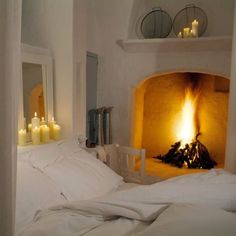 This is a house with a lovely white stucco Bedroom & the fireplace looks so cozy.In fact, the room has the ambiance of a residence on a Greek Island.