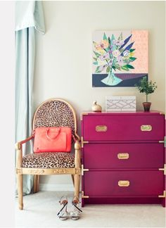 Hot pink dresser with brass pulls and the brass/gold bird sitting on top.