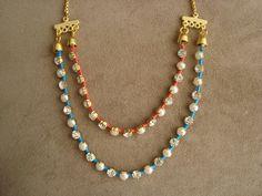 Maxi colar confeccionado em correntes de metal dourado com aplicação de pérolas síntéticas e strass branco. O toque de cor fica por conta das linhas nas cores azul turquesa e rosa neon. R$78,00