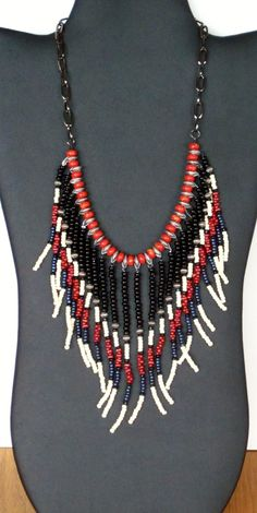 Multiple strands of black, cream, coral, blue-violet and silver seed beads. The strands are attached to silver plate discs, and separated by coral beads. The necklace is finished with gunmetal black chain with a hook closure. The total length is about 17.5 long, the longest fringes are 4 long.