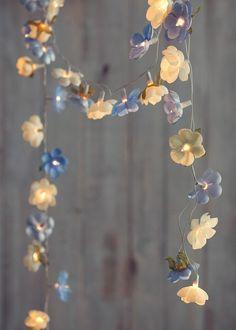 Sabe as luzinhas de Natal que ficam guardadas no armário o ano todo? Use-as para decorar a sua casa. Com camélias de tecido, o efeito fica muito romântico e delicado. (Foto: Cacá Bratke/Casa e Comida)