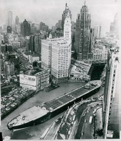 "The barge ""Marine Angel"" negotiates a turn through the upraised Michigan Ave. bridge, Chicago, 1953."
