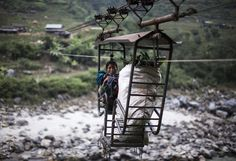 A local Nepalese woman crosses the Trishuli River using a rope bridge, known locally as a Tuin, near the village of Fhading Village in Dhading Disrict, some 90 kilometers from capital Kathmandu, Nepal, December 4, 2014. Farmers, students and villagers from the other side of the Trishuli river have to use different methods to cross after local authorities failed to build a promised bridge. (EPA/NARENDRA SHRESTHA)