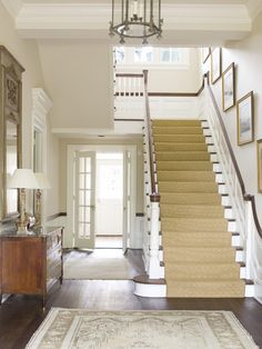 I love the wall color used in this foyer along with the seagrass on the stairs. The pictures going up the stairs as well.
