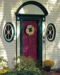 Welcome guests to you home wedding with a fresh flower wreath on the front door.